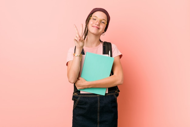 Young caucasian woman holding some notebooks showing number two with fingers.