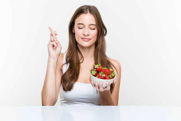Young caucasian woman holding a strawberries bowl crossing fingers for having luck