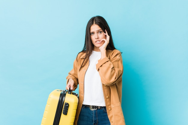 Young caucasian woman holding a suitcase biting fingernails, nervous and very anxious.