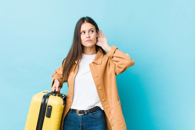 Young caucasian woman holding a suitcase trying to listening a gossip.
