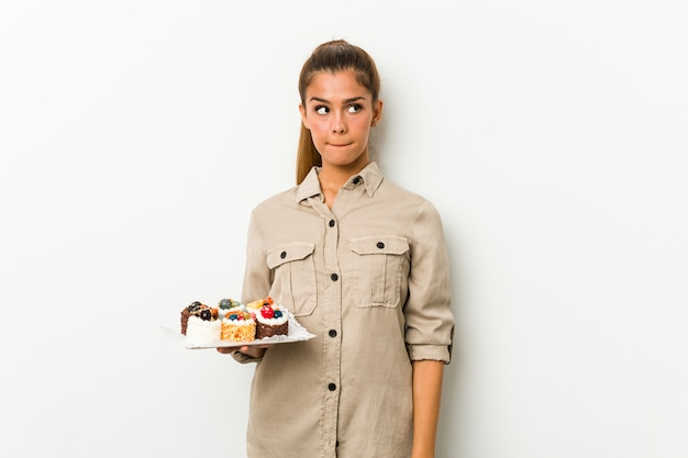 Young caucasian woman holding sweet cakes confused, feels doubtful and unsure.