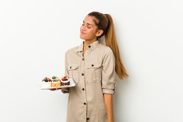 Молодая кавказская женщина, держащая сладкие пирожные, мечтающая о достижении целей и задач