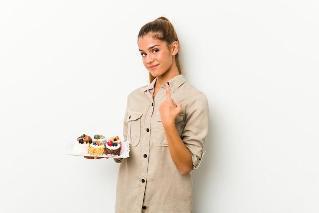 Молодая кавказская женщина держит сладкие пирожные, указывая пальцем на вас, как будто приглашая подойти ближе.