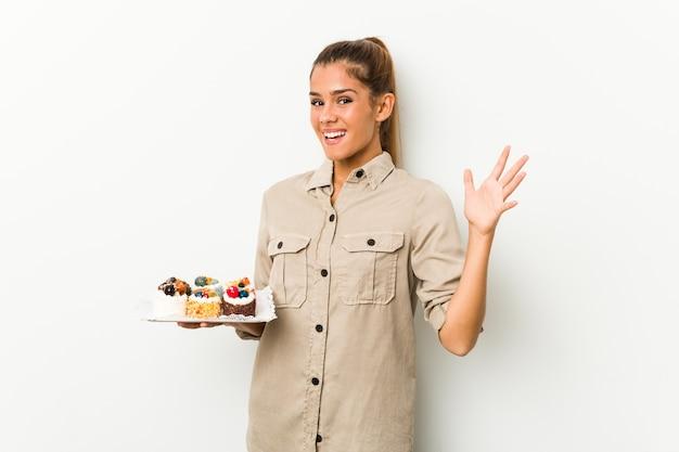 Молодая кавказская женщина, держащая сладкие пирожные, получает приятный сюрприз, взволнована и поднимает руки.