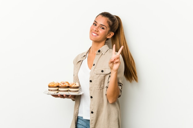 Young caucasian woman holding sweet cakes showing number two with fingers.