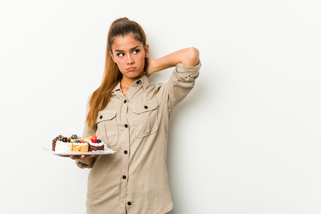 Young caucasian woman holding sweet cakes touching back of head, thinking and making a choice.
