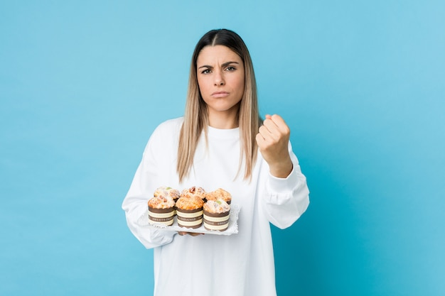 Young caucasian woman holding a sweets cake showing fist to with aggressive facial expression.