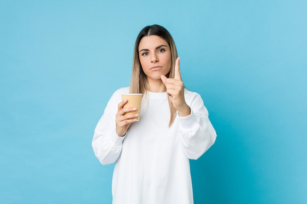 Young caucasian woman holding a takeaway coffee showing number one with finger.
