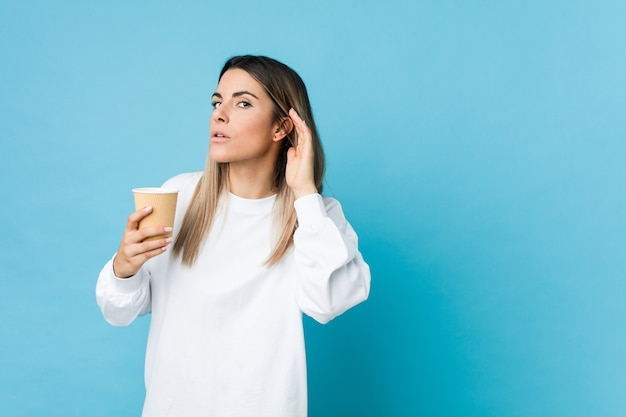 Young caucasian woman holding a takeaway coffee trying to listening a gossip.