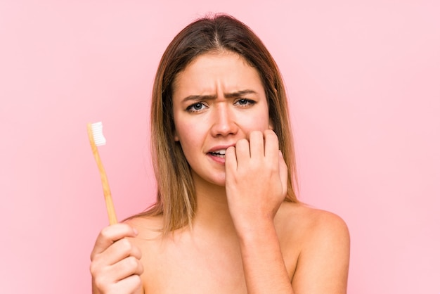Young caucasian woman holding a teeth brush isolated biting fingernails, nervous and very anxious.