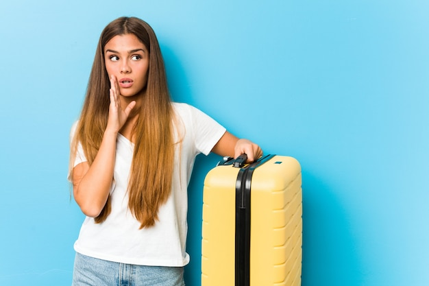 Young caucasian woman holding a travel suitcase is saying a secret hot braking news and looking aside