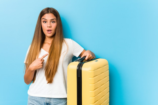 Young caucasian woman holding a travel suitcase pointing to the side