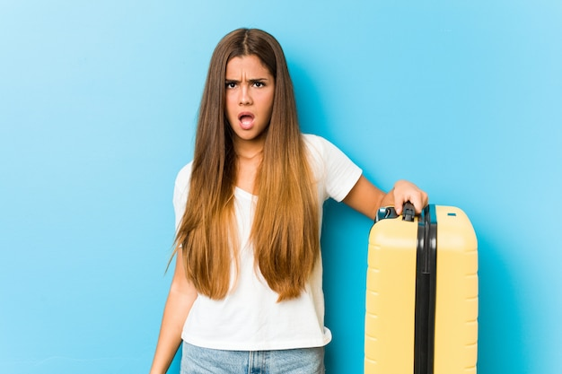Young caucasian woman holding a travel suitcase screaming very angry and aggressive.