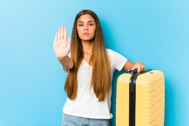 Young caucasian woman holding a travel suitcase standing with outstretched hand showing stop sign, preventing you.