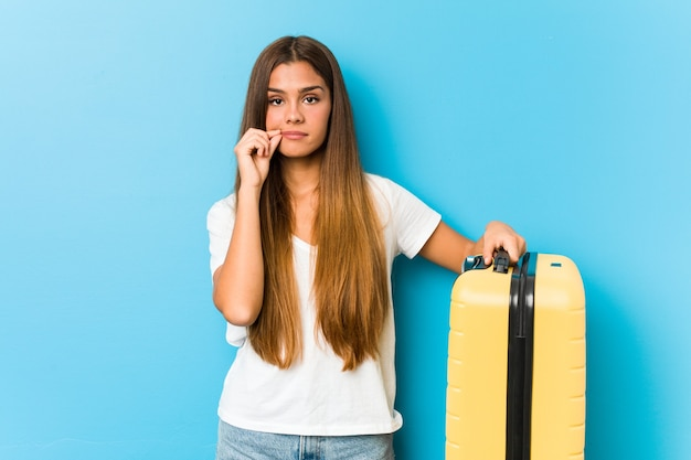 Young caucasian woman holding a travel suitcase with fingers on lips keeping a secret.