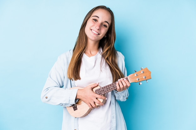 Young caucasian woman holding a ukelele isolated happy, smiling and cheerful.