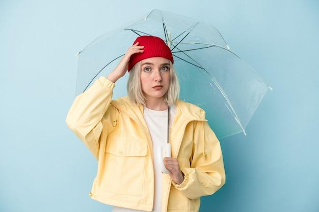 Молодая кавказская женщина, держащая зонтик на синем фоне в шоке, вспомнила важную встречу.