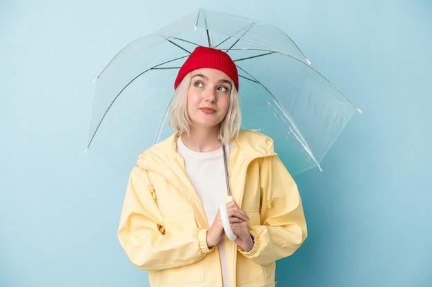 目標と目的を達成することを夢見て青い背景に分離傘を保持している若い白人女性