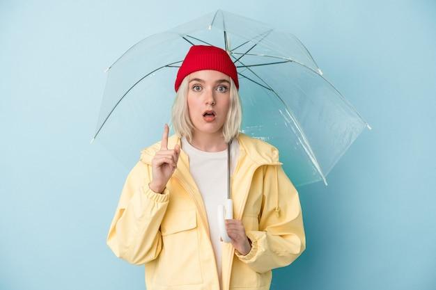 Молодая кавказская женщина, держащая зонтик, изолирована на синем фоне, имея идею, концепцию вдохновения.