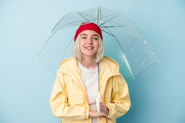 Молодая женщина кавказской, держащая зонтик, изолированные на синем фоне, смеясь и весело.