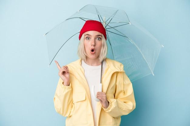 Молодая кавказская женщина, держащая зонтик на синем фоне, указывая в сторону