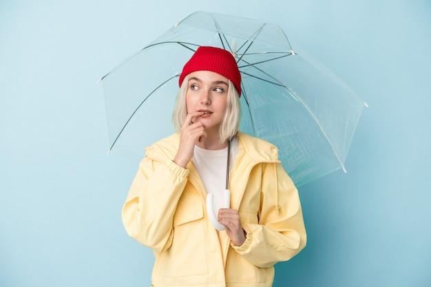 Молодая кавказская женщина, держащая зонтик, изолированная на синем фоне, расслабилась, думая о чем-то, глядя на копию пространства.