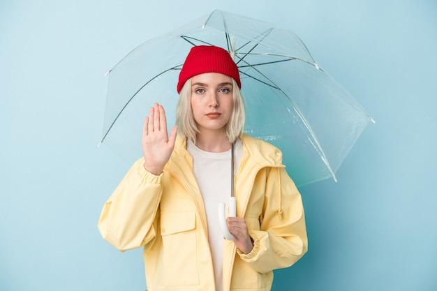 Молодая кавказская женщина, держащая зонтик, изолирована на синем фоне, стоя с протянутой рукой, показывая знак остановки, предотвращая вас.
