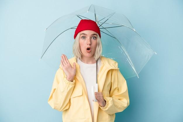 青い背景に分離された傘を持っている若い白人女性は驚いてショックを受けました。