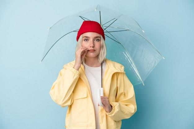 Молодая кавказская женщина, держащая зонтик, изолирована на синем фоне с пальцами на губах, сохраняя в секрете.