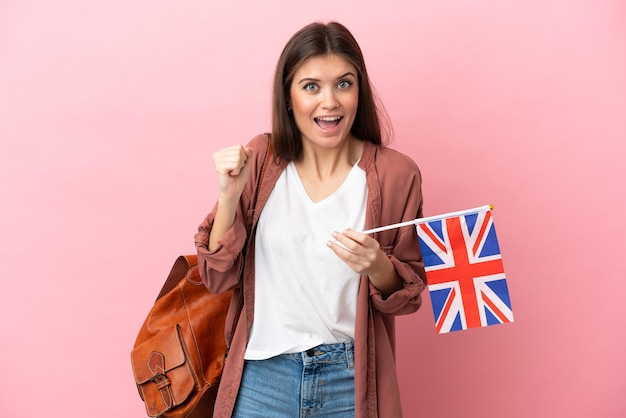 Young caucasian woman holding an united kingdom flag isolated on pink background celebrating a victory in winner position