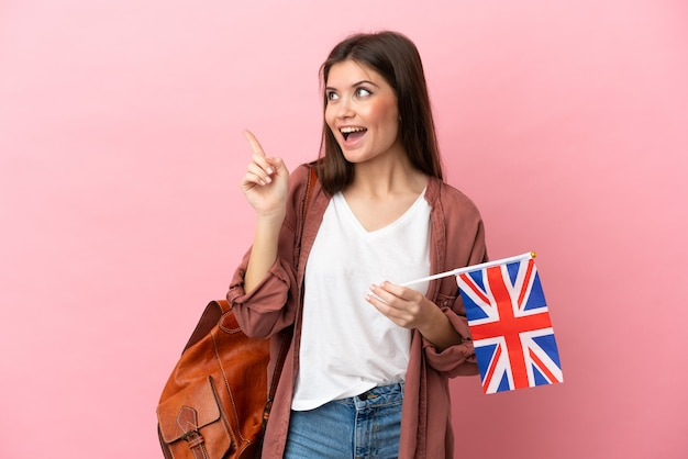 Young caucasian woman holding an united kingdom flag isolated on pink background intending to realizes the solution while lifting a finger up