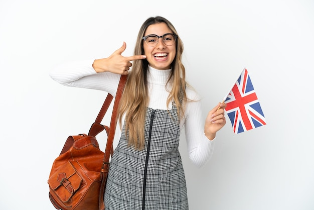 Young caucasian woman holding an united kingdom flag isolated on white background giving a thumbs up gesture