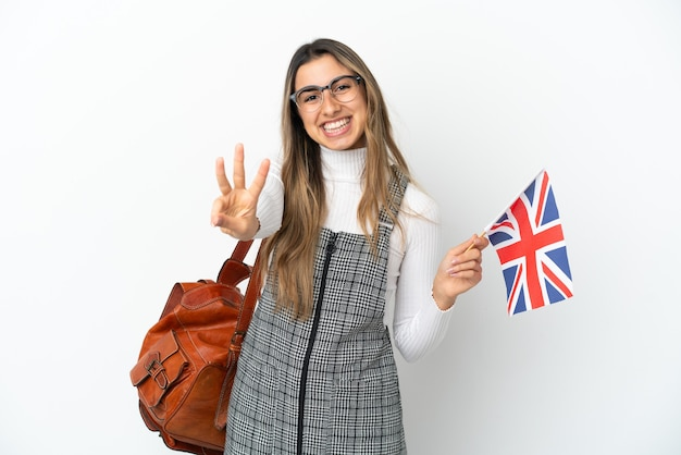 Young caucasian woman holding an united kingdom flag isolated on white background happy and counting three with fingers