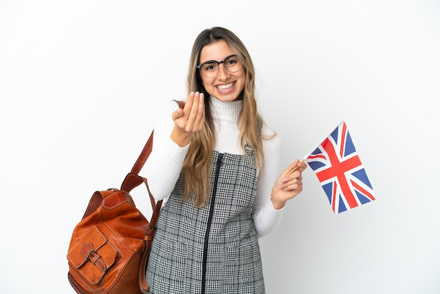 Young caucasian woman holding an united kingdom flag isolated on white background inviting to come with hand. happy that you came