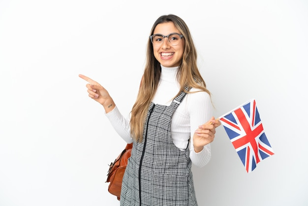 Young caucasian woman holding an united kingdom flag isolated on white background pointing finger to the side
