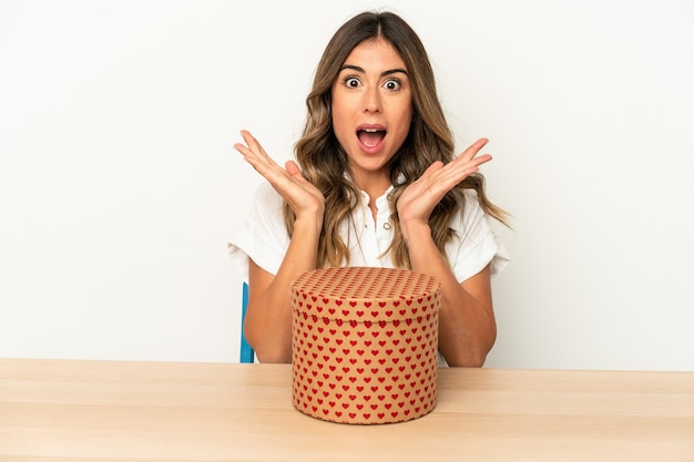 Young caucasian woman holding a valentines day box isolated surprised and shocked.