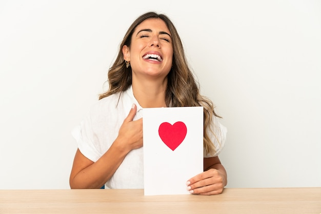 Young caucasian woman holding a valentines day card isolated laughs out loudly keeping hand on chest.