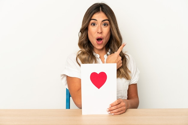 Young caucasian woman holding a valentines day card isolated pointing to the side