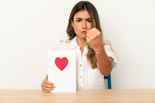 Young caucasian woman holding a valentines day card isolated showing fist to camera, aggressive facial expression.
