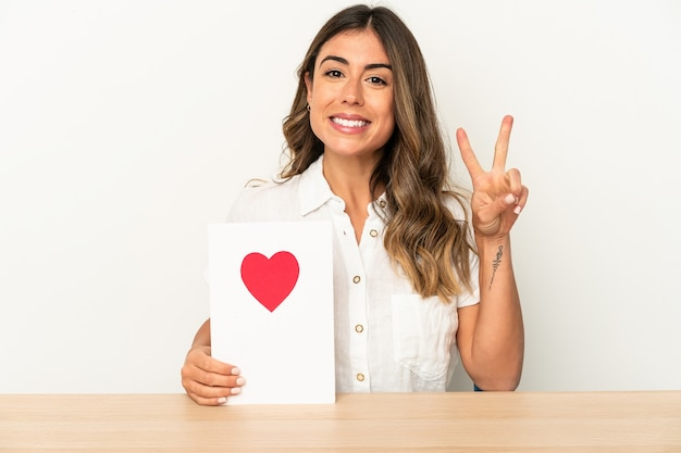 Young caucasian woman holding a valentines day card isolated showing number two with fingers.