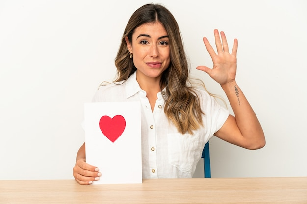 Young caucasian woman holding a valentines day card isolated smiling cheerful showing number five with fingers.