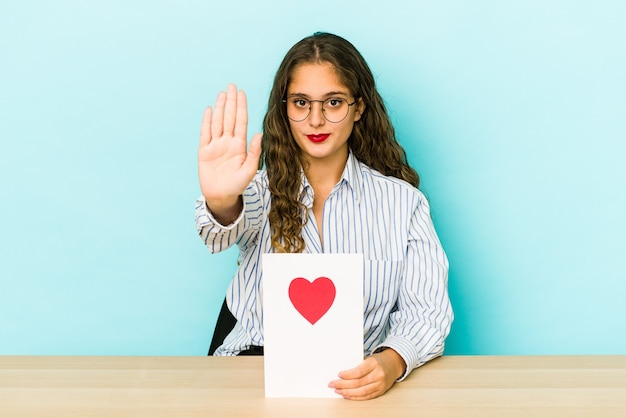 Young caucasian woman holding a valentines day card isolated standing with outstretched hand showing stop sign, preventing you.