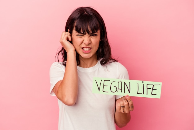 Young caucasian woman holding a vegan life placard isolated on pink background covering ears with hands.