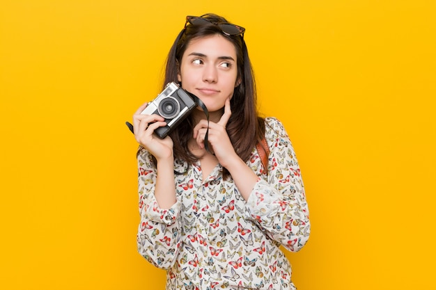 Young caucasian woman holding a vintage camera