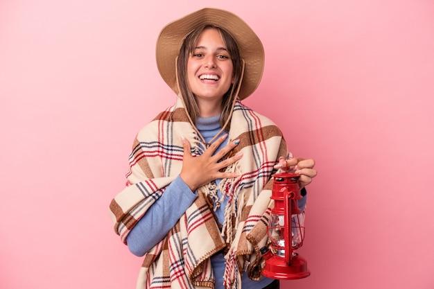 ピンクの背景に分離されたヴィンテージのランタンを保持している若い白人女性は、胸に手を置いて大声で笑います。