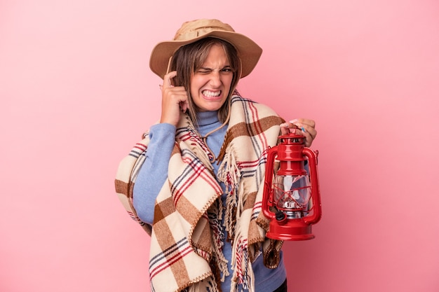 Young caucasian woman holding vintage lantern isolated on pink background covering ears with hands.
