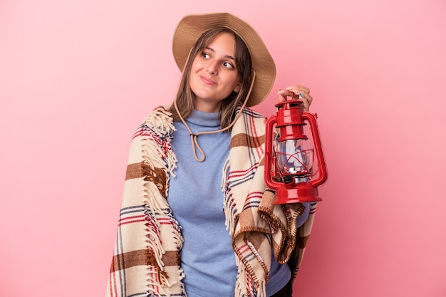 Young caucasian woman holding vintage lantern isolated on pink background dreaming of achieving goals and purposes