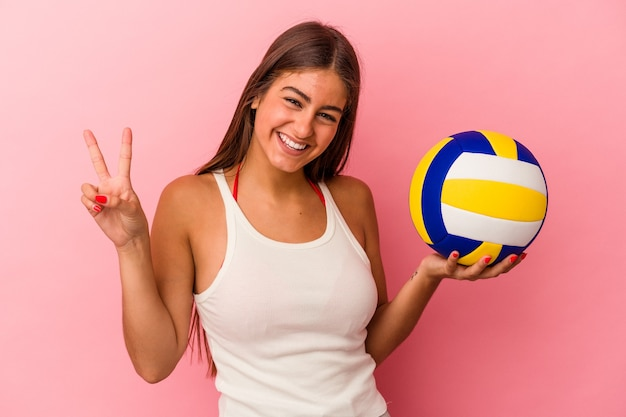 Young caucasian woman holding a volleyball ball isolated on pink background joyful and carefree showing a peace symbol with fingers.