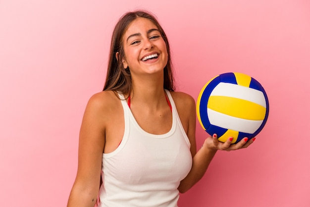 Young caucasian woman holding a volleyball ball isolated on pink background laughing and having fun.