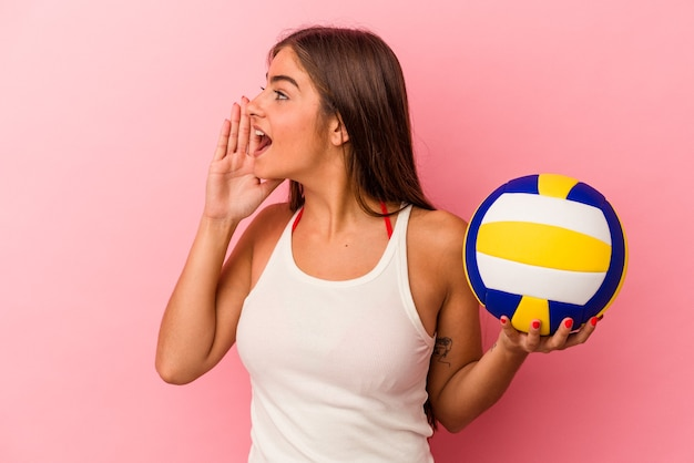 Young caucasian woman holding a volleyball ball isolated on pink background shouting and holding palm near opened mouth.